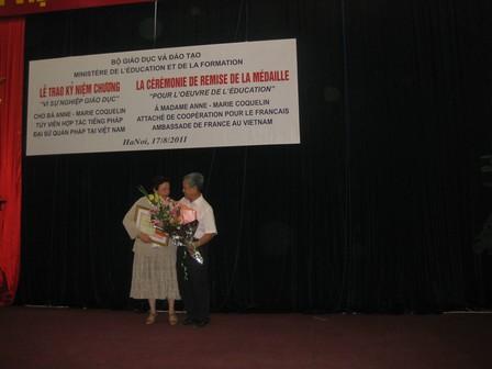 M.NGUYEN Duc Chinh, directeur du programme PFIEV, remet un bouquet de fleurs à Madame Anne Marie Coquelin - 33.3ko